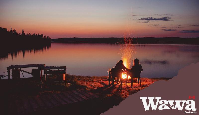 An image of two people sitting by a camp fire in Wawa.